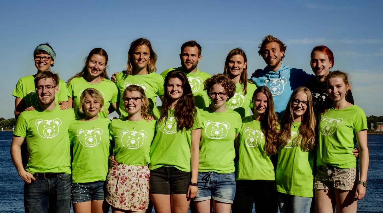Die Mitglieder des TBK Orga Teams Kiel posieren vor der Kieler Förde auf einem Gruppenfoto